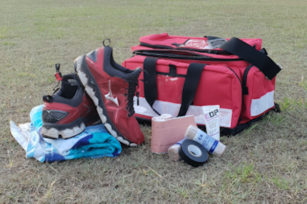 First Aid bag, medical and sports gear, used by a Sports Trainer. The gear is sitting on a grass oval